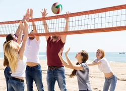 happy group of friends having fun at beach and playing ball