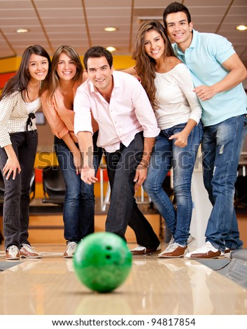 Happy group of friends having fun bowling