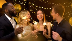 Happy group of friends holding bengal lights and wine glasses, New Year greeting