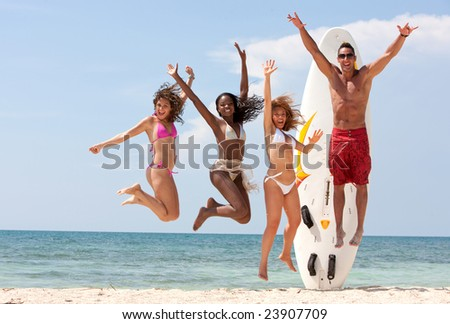 Happy group of friends jumping full of joy at the beach