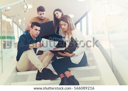 Happy group of friends sitting on the stairs in the school or college