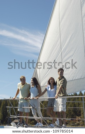 Happy group of friends standing together on sailboat