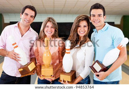Happy group of friends winning a bowling trophy