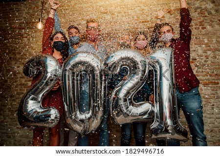 Happy group of friends with face mask celebrating new 2021 year - Confetti falling in the air - Young people with balloons in hands making new year party at home - Focus on balloons.