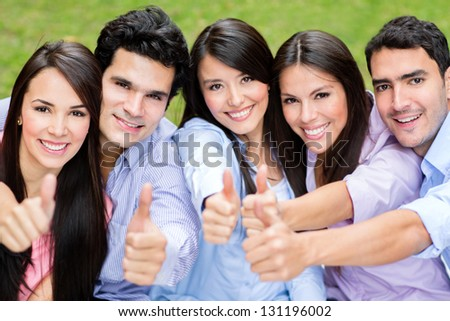 Happy group of friends with thumbs up outdoors
