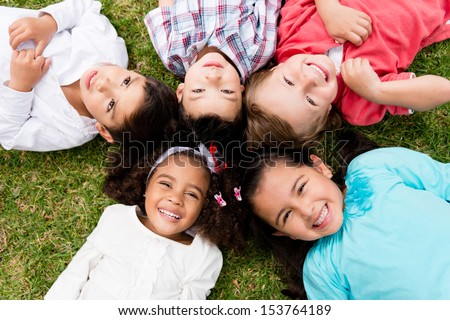 Happy group of kids lying on the floor in a circle