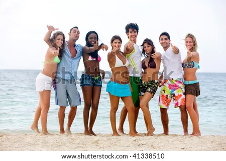 Happy group of people at the beach with thumbs up