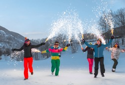Happy group of people having fun on winter vacation - Friends witn snow suit partying outdoors