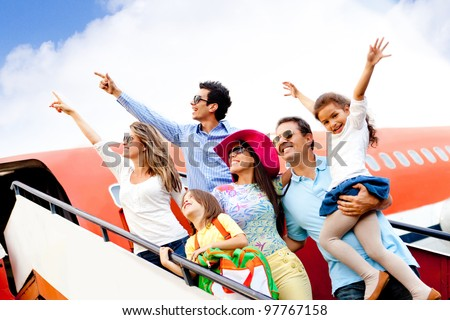 Happy group of people traveling by airplane on their holidays