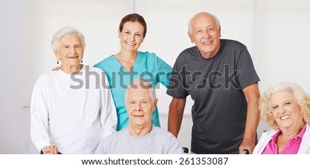Happy group of senior citizens in nursing home with geriatric nurse