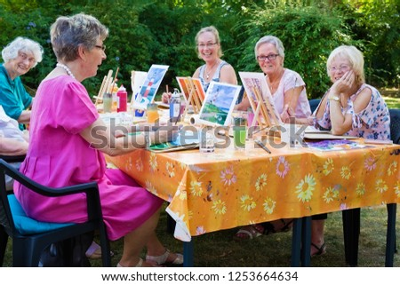 Happy group of senior ladies enjoying art class seated around a table outdoors in the garden painting with water colors while smiling and chatting.