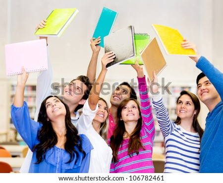 Happy group of students celebrating with arms up