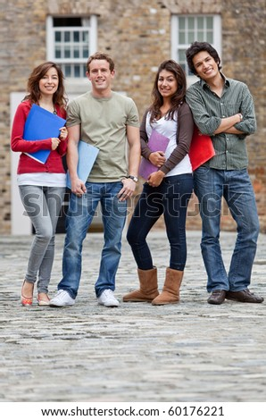 Happy group of students outdoors holding notebooks