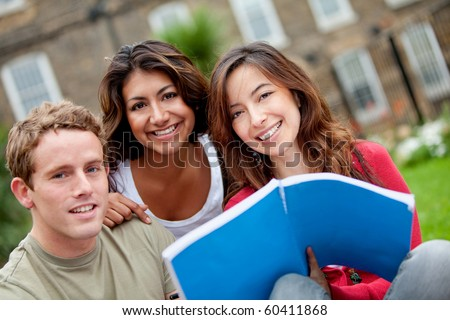 Happy group of students with a notebook outdoors