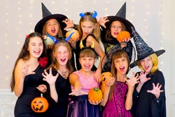Happy group of teenagers in Halloween costumes posing on camera with pumpkins, smiling and joking