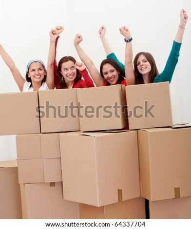 Happy group of women with cardboard boxes moving into a new house . - stock photo