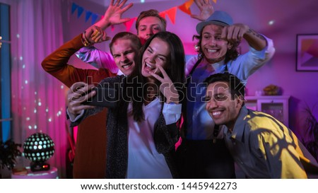 Happy Group of Young People Taking Collective Selfie at the Wild House Party. Neon Lights, Disco Ball and Funny Costumes.