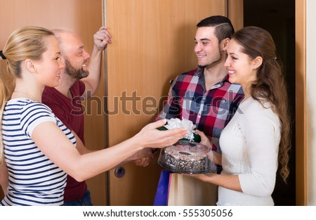 Happy guests with presents and cake standing in doorway. Focus on girl Сток-фото ©