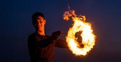Happy guy artist perform fire circle by spinning burning poi on idyllic dark sky at night outdoors, orbital.