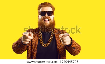 Happy guy in gold necklace and leopard suit pointing fingers at camera isolated on color background. Famous fashion designer, rich showbiz producer, casting director, funny celebrity says I choose you
