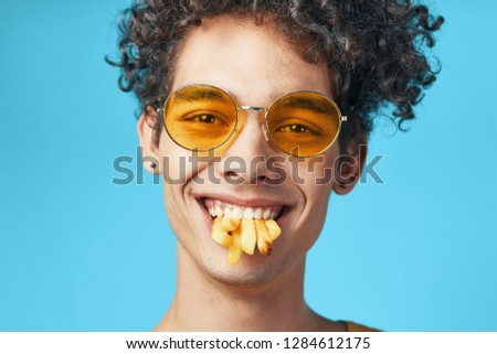 Happy guy in yellow glasses eats french fries