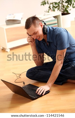 Happy guy is listening music from laptop through headphones