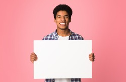 Happy guy showing blank placard with copy space for your text, pink background