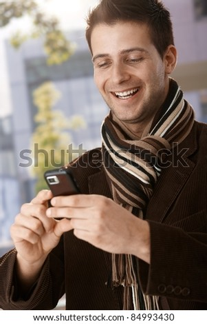 stock-photo-happy-guy-wearing-scarf-looking-at-mobile-phone-handheld-laughing-84993430.jpg