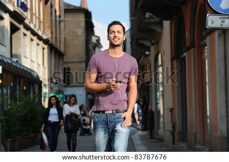 happy guy while talking on the phone to the streets of his city