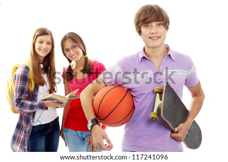 Happy guy with ball and skateboard on background of two cute girls