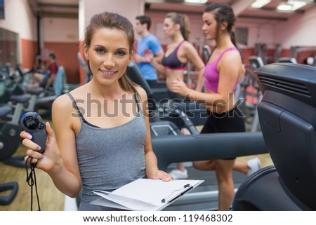 Happy Gym instructor showing stopwatch in the gym