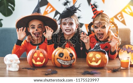 happy Halloween! a group of children in suits and with pumpkins in the home