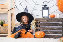 Happy Halloween. A little beautiful girl in a witch costume celebrates a home in an interior with pumpkins