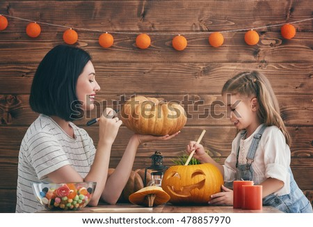 Happy halloween A mother and her daughter carving pumpkin. Happy family preparing for Halloween.