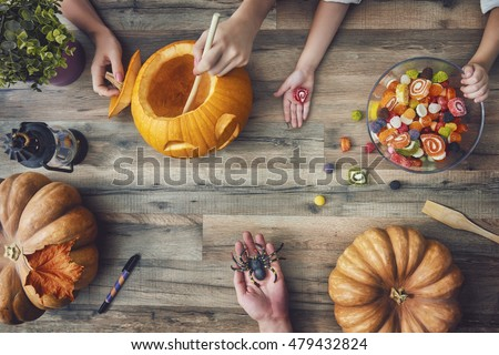Happy halloween! A mother, father and their daughter carving pumpkin on the table in the home. Family preparing for Halloween.