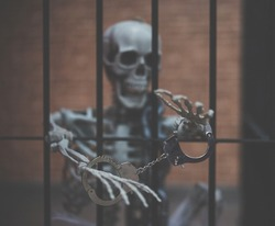 Happy Halloween. A skeleton is trapped in cage. dark and gloomy processed in vintage style with film grained. Soft focus. Imprison to death concept for Halloween.