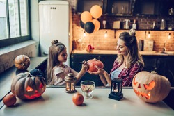 Happy Halloween! Attractive young pregnant woman with her little cute daughter are preparing to Halloween on kitchen. Mom with daughter are having fun with pumpkins while painting it.