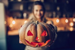 Happy Halloween! Attractive young woman is preparing to Halloween on kitchen. Beautiful woman with pumpkins.