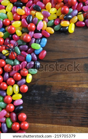 Happy Halloween candy with spiders on rustic dark wood background with copy space for your text here.