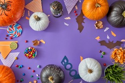 Happy halloween! Carving pumpkin, candy, paper bats on the table in the home. Preparing for holiday.
