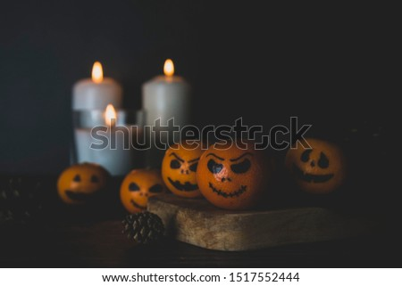 Happy Halloween citrus, tangerines painted with scary, funny faces. Dark photo with candles. Alternatives to traditional Halloween pumpkins. Creative autumn composition.