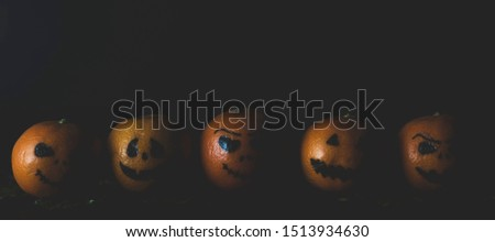 Happy Halloween citrus, tangerines painted with scary, funny faces. Dark photo with copy space for copy space.