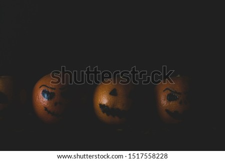 Happy Halloween citrus, tangerines painted with scary, funny faces. Dark photo with copy space for copy space. #1517558228