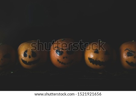 Happy Halloween citrus, tangerines painted with scary, funny faces. Dark photo with copy space for copy space. #1521921656