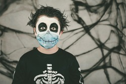 Happy Halloween.Close-up of kid wearing medical mask in a skeleton costume 