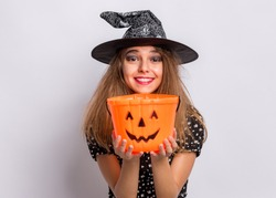 Happy halloween concept. Smiling teen girl in witch black hat holding orange pumpkin bucket on grey background. Joyful young teenager in witch halloween costume looking at camera, waiting candy.