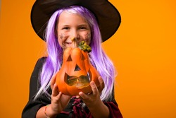 Happy Halloween! Cute cheerful little witch in a carnival costume and a pumpkin in her hands. A beautiful childish girl on a yellow background conjures and laughs. Selective focus. High quality photo