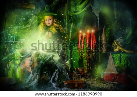 Happy Halloween. Cute child girl in witch costume is in a witch's lair. Cute cheerful little witch cooks a magic potion.  #1186990990