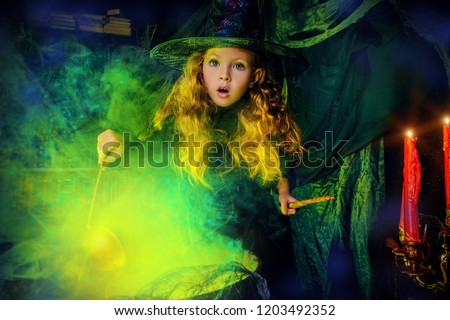Happy Halloween. Cute child girl in witch costume is in a witch's lair. Cute cheerful little witch cooks a magic potion.