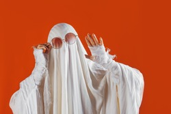 Happy Halloween. Cute funny Ghost on a bright orange background. Sheet Ghost costume, Halloween party carnival. Lovely ghost waving Hello